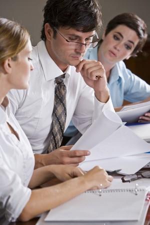 ビジネスマンを見て女性の同僚と文書を読む