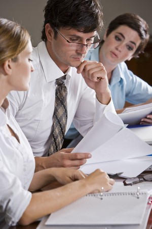 Businessman reading documents with female co-workers watching
