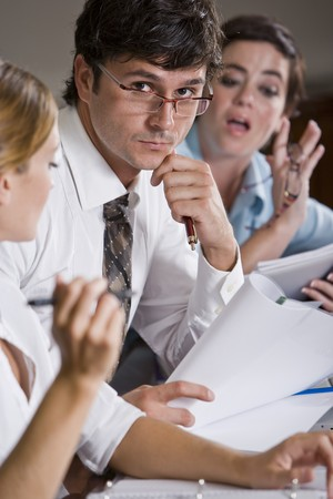 reviewing documents: Businessman reviewing documents with female co-workers watching Stock Photo