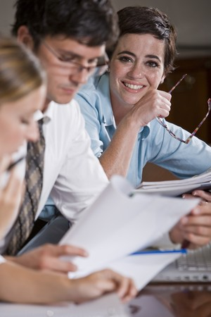 Female office worker with colleagues reading reports, focus on woman in background