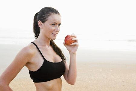 Side view of healthy fit young woman on beach eating apple photo