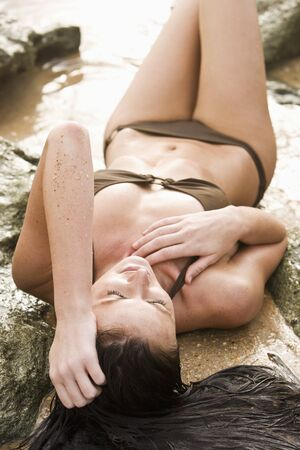 High angle view of beautiful young woman in bikini laying on rocky beach photo