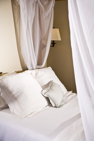 Pillows on a white canopy bed with curtains photo