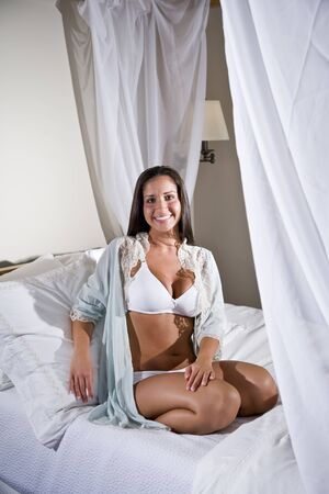 Sexy beautiful young Hispanic woman sitting on white canopy bed photo