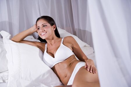 Sexy beautiful young Hispanic woman sitting on white canopy bed photo