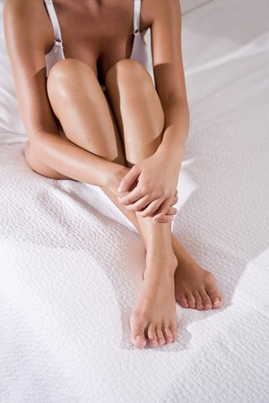 Low section of sexy woman with beautiful legs sitting on white bedspread Stock Photo