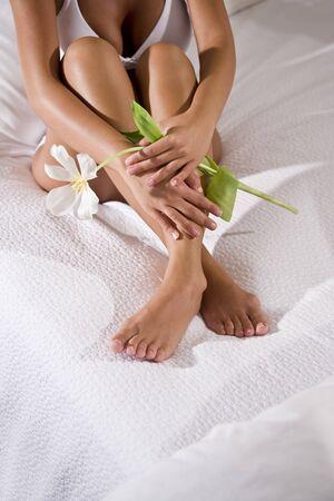 knees bent: Sezione bassa di sexy donna con le gambe belle azienda fiore seduta sul copriletto bianco