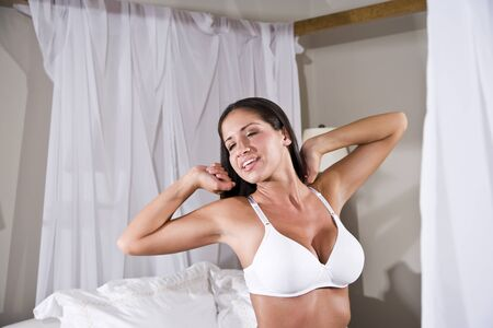 Beautiful young sexy Hispanic woman stretching in bed wearing underwear photo
