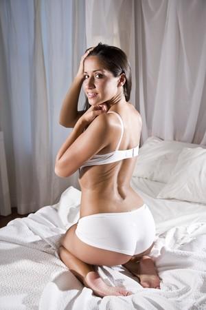 mujer arrodillada: Mujer sexy hermosa joven de hispanos en la cama vistiendo ropa interior