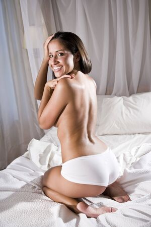 Beautiful young sexy Hispanic woman in bed wearing underwear photo