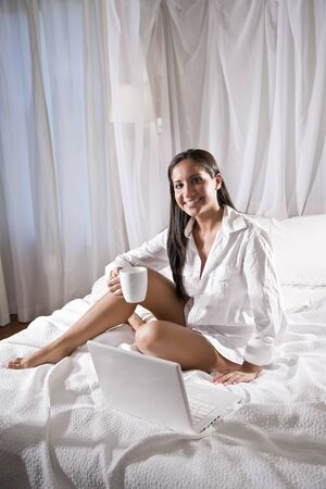 Beautiful young Hispanic woman sitting on bed drinking coffee photo