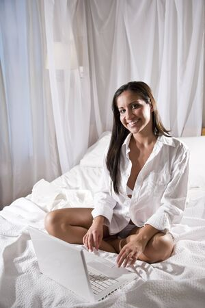 Beautiful sexy young Hispanic woman sitting on bed using laptop photo