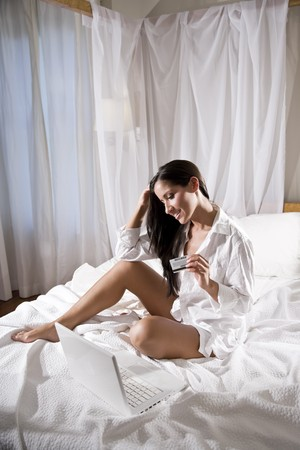 Sexy Hispanic woman sitting in bed shopping on internet holding credit card