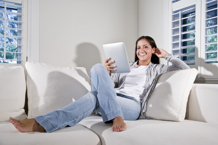 Hispanic woman reading electronic book relaxing on couch
