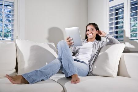 Spaanse vrouw lezen van elektronische boek ontspannen op bank Stockfoto - 7899033
