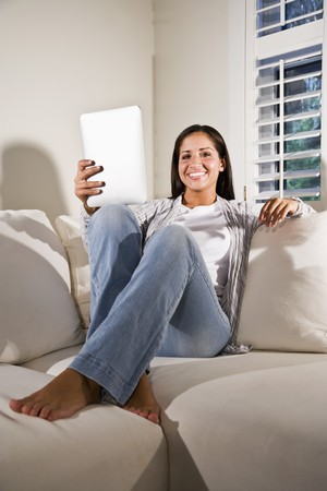 Hispanic woman reading electronic book relaxing on couch photo