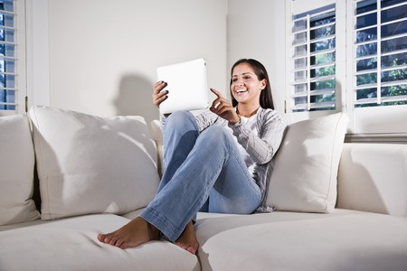 woman on couch: Hispanic woman using tablet computer relaxing on couch