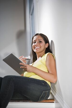 Beautiful young Hispanic woman, online shopping on tablet computer photo