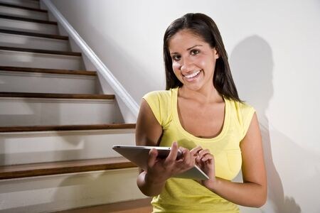 Beautiful young Hispanic woman using tablet computer on stairs photo