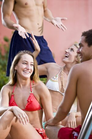Young couples chatting and laughing by swimming pool, focus on woman in red bikini photo