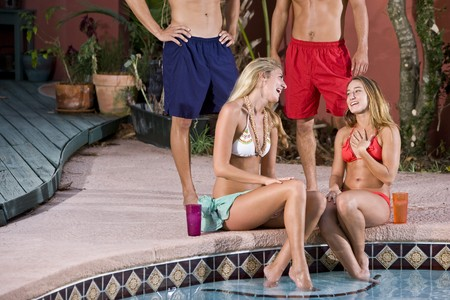 Two young couples by pool, women talking and laughing photo