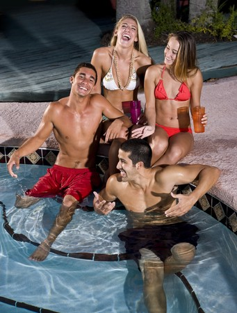 Young adult friends laughing together by swimming pool photo