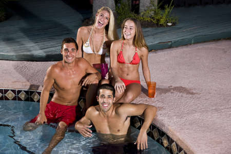 Young adult friends relaxing together by swimming pool photo