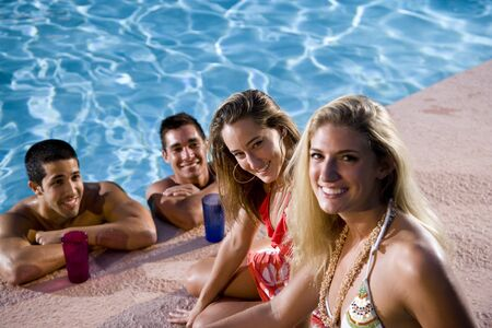 Young couples relaxing at swimming pool, focus on woman in red bikini photo