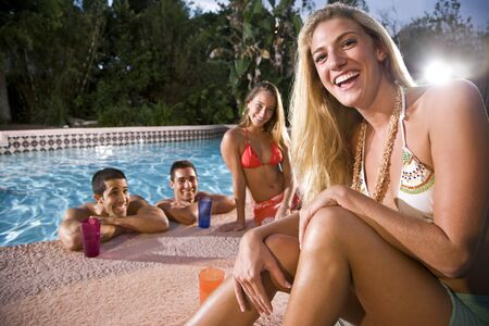 Young adults relaxing at swimming pool, focus on blond woman in foreground photo