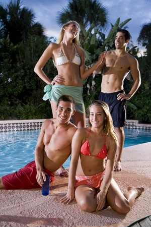 Young adult friends having fun together by swimming pool, focus on couple in foreground photo