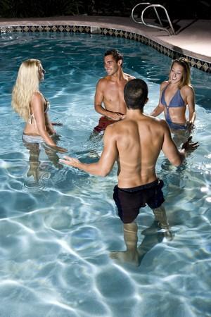 Young adults (20s) having fun in swimming pool at night Stock Photo - 8064006