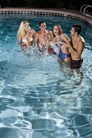 Young adults (20s) having fun in swimming pool at night photo