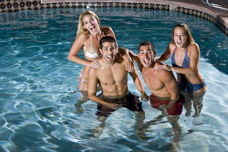 Young adults (20s) having fun in swimming pool at night photo