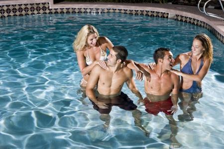 밤에는 수영장에서 즐거운 젊은 성인 (20 대)