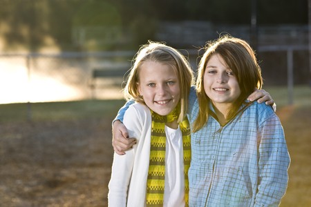 10 11 years: Young friends posing together in park on chilly fall morning Stock Photo