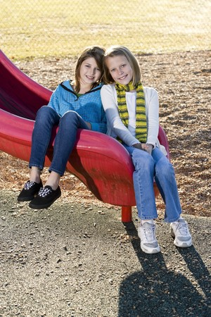 10 11 years: Close-up of young friends (10-11 years) posing together outdoors on playground slide Stock Photo