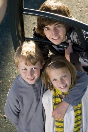 Three children (10 to 15 years) standing together on playground equipment Stock Photo - 8167702
