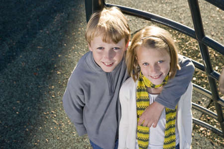 11 years: Brother and sister (10 and 11 years) posing together on playground Stock Photo