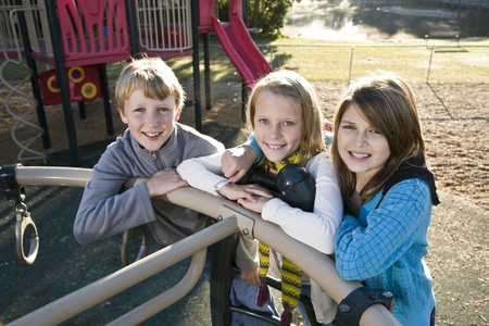 11 years: Three children (10 to 11 years) standing together on playground equipment