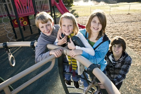 Group of children (10 to 15 years) standing together on playground equipment Stock Photo - 8191133