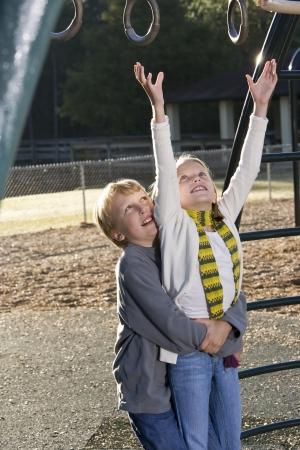 少年の遊び場にリングのために達する彼の妹を持ち上げる 写真素材