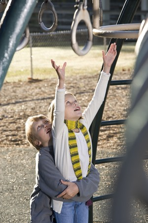 10 11 years: Boy lifting his sister, reaching up for rings on playground Stock Photo