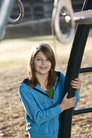 11 years: Happy young girl (11 years) standing by playground equipment