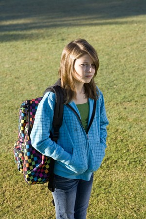 11 years: Child (11 years) carrying bookbag over her shoulder, with serious expression on face