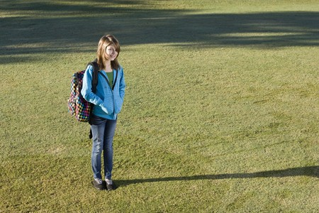 Smiling child (11 years) carrying bookbag over her shoulder, standing on grass photo