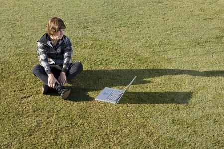 15 歳の少年は公園で彼のラップトップ上でオンラインに 写真素材