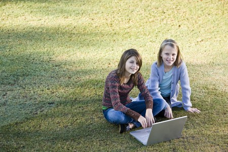 11 years: Two young friends (10 and 11 years) using laptop together outdoors in park