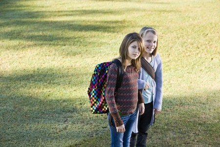 11 years: Two elementary school girls (10 and 11 years) carrying their bookbags Stock Photo