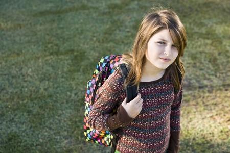 Meisje (11 jaar) uitvoering school rugzak, op zoek naar camera met ernstige expressie Stockfoto