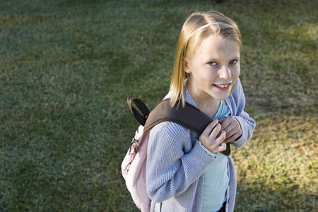 Girl (10 years) carrying school backpack, looking at camera smiling photo